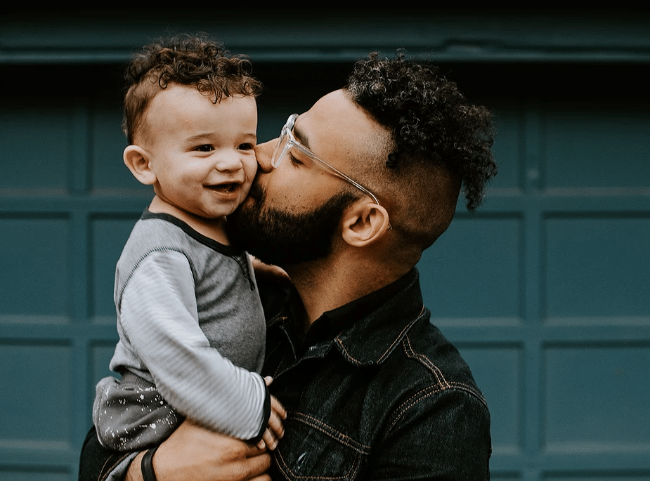 Dad with glasses kissing his kid